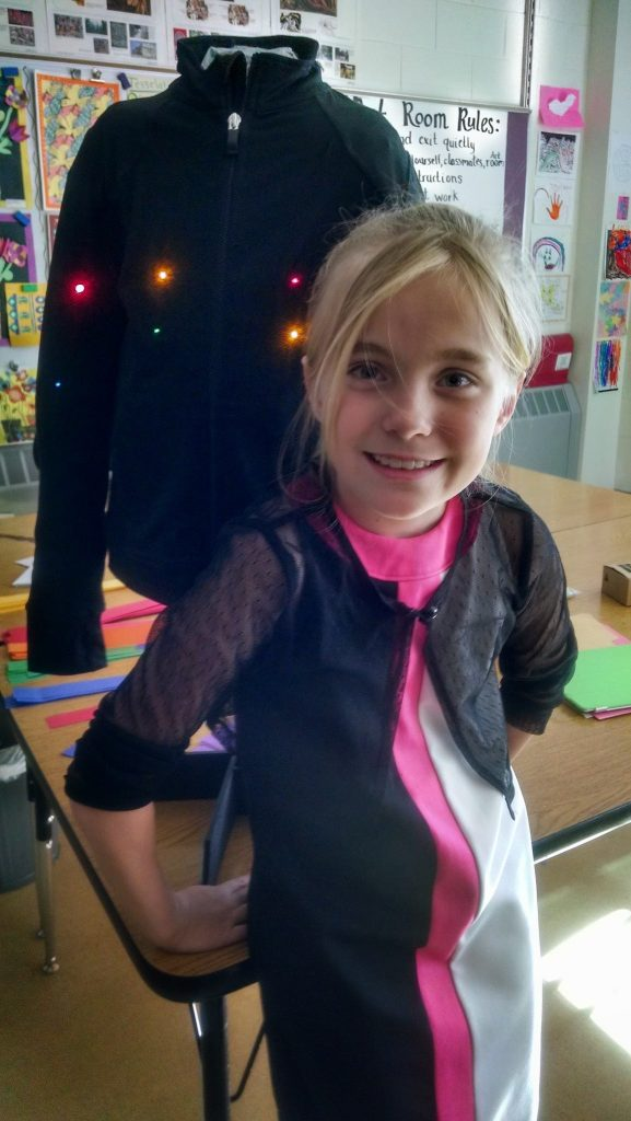Kata, grade 4, with the LED jacket she designed to increase a runner's visibility at night. STEAM workshop: Textiles + TechStyles.