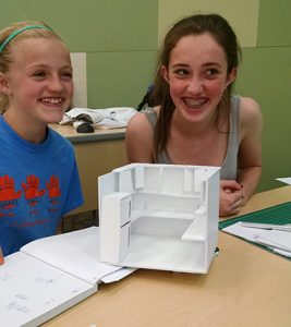 Madeleine and her teammate Kyra work on their scale model for the Habitat for Humanity kitchen and undercabinet lighting.