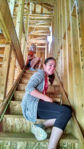 Madeleine and her teammate Autumn wire the stairway of a Habitat for Humanity home in preparation to install LED puck lighting.