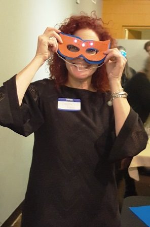Girls in STEAM teach guests to blend science and art. Dawn Putney with her finished mask.